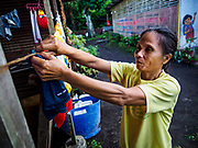 20 JANUARY 2018 - CAMALIG, ALBAY, PHILIPPINES: ARLENE NAGA hangs her laundry at the Barangay Cabangan evacuee shelter in a school in Camalig. There are about 650 people living at the shelter. They won't be allowed to move back to their homes until officials determine that Mayon volcano is safe and not likely to erupt. More than 30,000 people have been evacuated from communities on the near the Mayon volcano in Albay province in the Philippines. Most of the evacuees are staying at school in communities outside of the evacuation zone.   PHOTO BY JACK KURTZ