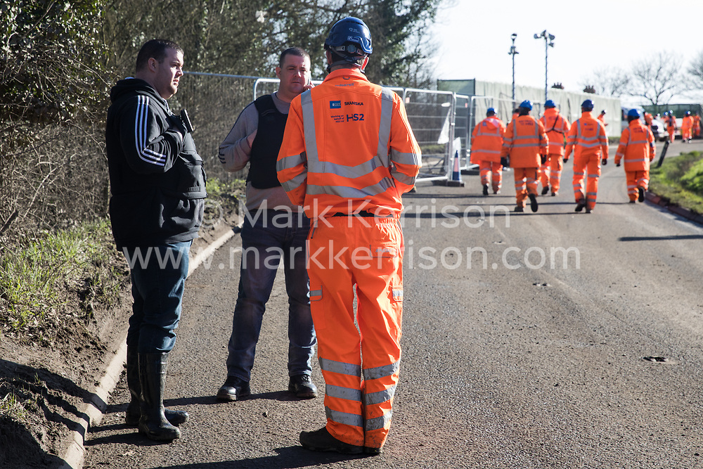 Harefield, UK. 8 February, 2020. A senior HS2 engineer talks to ASB officers from Hillingdon Council after HS2 were forced to suspend tree felling works alongside Harvil Road in the Colne Valley by direct action from environmental activists based at a series of wildlife protection camps in the area. Road and rail closures had been implemented for the works.
