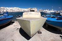 Una barca in vetroresina spicca in mezzo alle piu tradizionali imbarcazioni in legno nella darsena del porto di Gallipoli (LE)