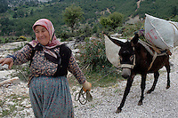 Turkish  woman on the road with theur donkey loaded up with crops in hills of Anatolia Southern Turkey.