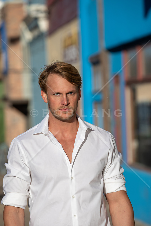 Portrait of a blond blue eyed man in a white button down shirt