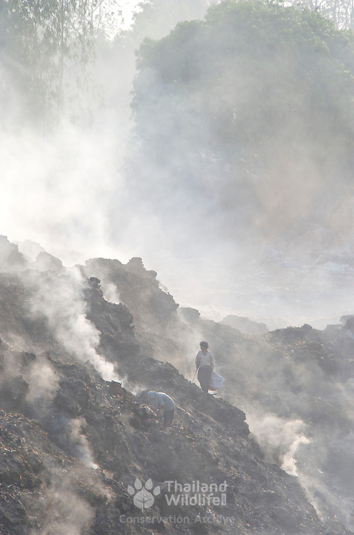 The poorest of people in Ratchaburi, considered to poorest of Thailand's provinces, searching a burning landfill for metal to salvage and sell as scrap.