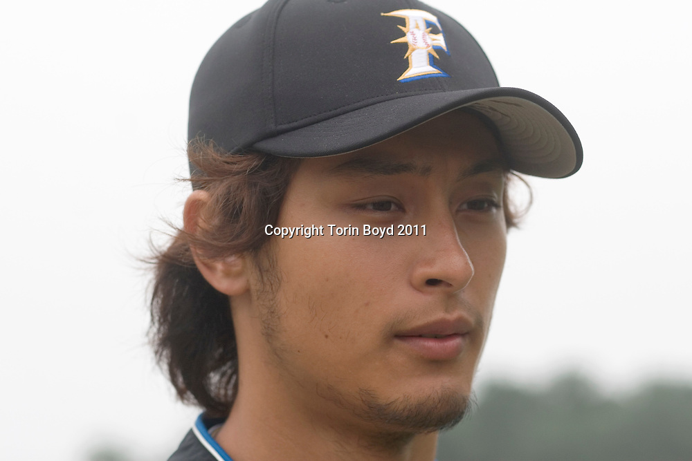 "This is Yu Darvish, the 21 year old Japanese baseball pitching sensation who's a starting pitcher for the Hokkaido Nippon Ham Fighters. Darvish is entering his fourth season with the team and is seen here during Spring training at the Fighters training camp in Nago City, Okinawa. Born in Japan on August 16, 1986 to an Iranian businessman and Japanese mother, Darvish caught the public's eye after pitching a no hitter during the Koshien high school baseball tournament in 2004 during his senior year for Tohoku High School (and fourth year at Koshien). This led to him being pursued by both Japanese and the Major League teams and was drafted by the Fighters. Darvish is listed as 6'5"" tall (196 cm) and 185 pounds (85 kg) and wears the number 11. Although there is much speculation he will one day move onto the Major Leagues, Darvish was quoted (during this interview) that he has no intentions of leaving Japan. He will also represent Japan in the 2008 Summer Olympics in Beijing. Photo taken at the Nago Stadium in Nago City, Okinawa on February 23, 2008."