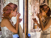 17 MARCH 2015 - BANGKOK, THAILAND: A woman puts on her makeup for prewedding photos in the old Customs House in Bangkok. With its evocative architecture and turn of the century mood, the Customs House is a popular setting for wedding photos and portraits. The old Customs House was once the financial gateway to Thailand (before 1932 called Siam). It was designed by an Italian architect in the 1880s. In the 1950s, customs moved to new, more modern building and the Customs House became the headquarters for the Marine firefighters. The firefighters now live in the decrepit buildings with their families.    PHOTO BY JACK KURTZ