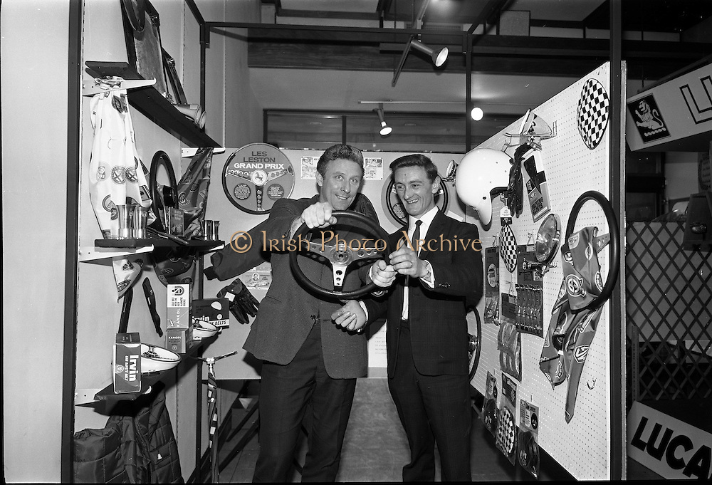 "26/06/1967<br /> 06/26/1967<br /> 26 June 1967<br /> Motoring Enthusiasts Week officially opened by Joe Lynch at the International Trade Promotion Centre, Dublin. Joe Lynch (Left) asks Mr. P. Byrne of Paddy Hopkirk Ltd. if he would care to ""Take the wheel?"" as he examines a Safety Steering wheel on the Paddy Hopkirk Ltd. stand."