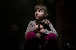 Ukraina<br /> <br /> Angelica 5, tillsammans med sin iller Jora. Angelica är blyg och ofta rädd. När byn blir beskjuten med granateld tar hon och hennes familj skydd i hallen i lägenheten. Det är den säkraste platsen de har att ta skydd på. Hon bor i Jilploschadka en förort till Donetsk.<br /> <br /> Photo: Niclas Hammarström