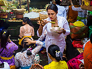 "02 AUGUST 2017 - UBUD, BALI, INDONESIA: People get holy water during the ""Merchants' Day"" ceremony at the Pura (Temple) Melanting Pasar Ubud, the small Hindu temple in the Ubud market. It's a day that merchants throughout Ubud come to the temple to make offerings and pray for prosperity.    PHOTO BY JACK KURTZ"
