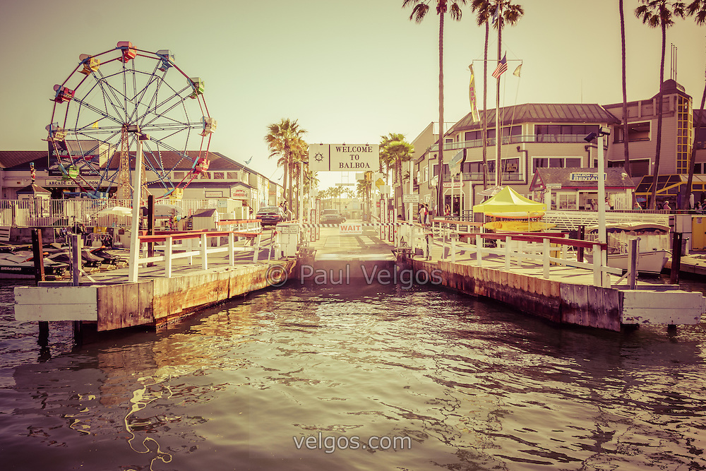 Newport Beach Balboa Island Ferry dock photo with the Welcome to Balboa sign and Balboa Fun Zone Ferris Wheel. Picture has a vintage style tone applied. The Balboa Island Ferry transports cars and people across Newport Harbor between Balboa Island and Balboa Peninsula in Newport Beach California.