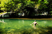 man wading naked into a fresh water swimming hole in Arkansas