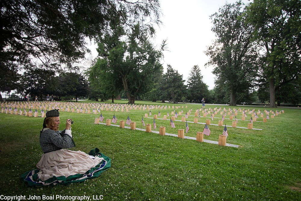 """Lisa Donnelly takes a moment in the shade to take a picture of the flags and luminaria set out at the Soldiers National Cemetery, during the Sesquicentennial Anniversary of the Battle of Gettysburg, Pennsylvania on Sunday, June 30, 2013.   Following """"A New Birth of Freedom"""" program at Meade's Headquarters, a procession by candlelight was led to the cemetery. John Boal photography"""