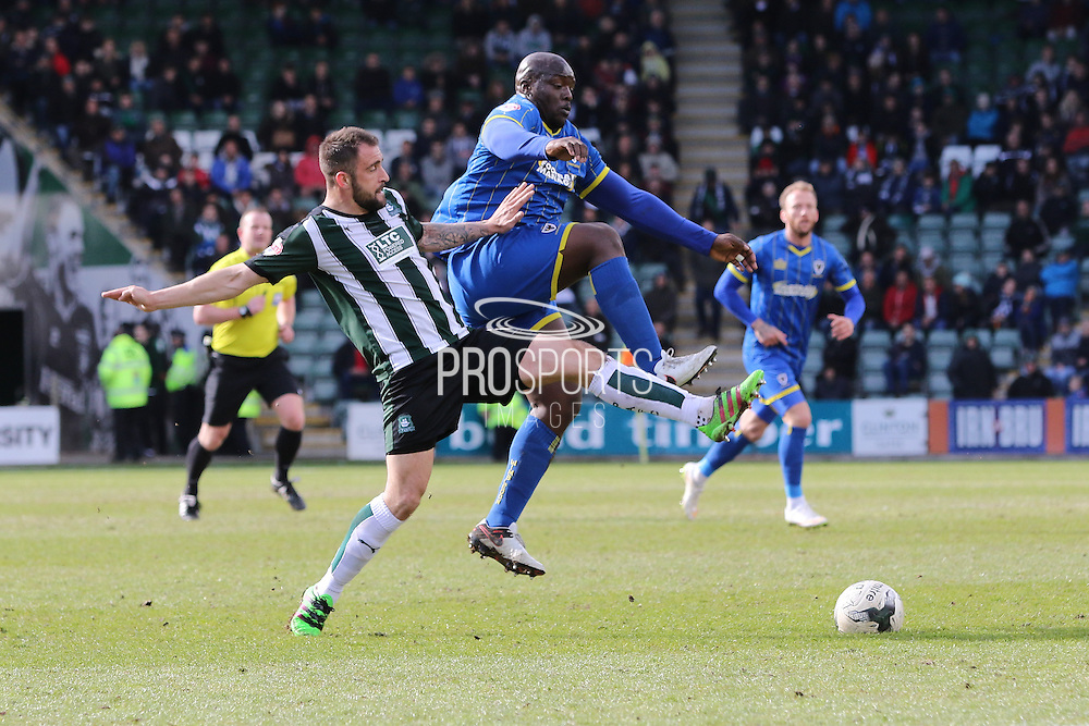 Bayo Akinfenwa forward for AFC Wimbledon (10) battles Plymouth Argyle defender Peter Hartley (6) during the Sky Bet League 2 match between Plymouth Argyle and AFC Wimbledon at Home Park, Plymouth, England on 9 April 2016. Photo by Stuart Butcher.