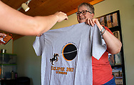 Sue Martindale displays an eclipse t-shirt for sale in Guernsey, Wyoming U.S. August 20, 2017.  REUTERS/Rick Wilking