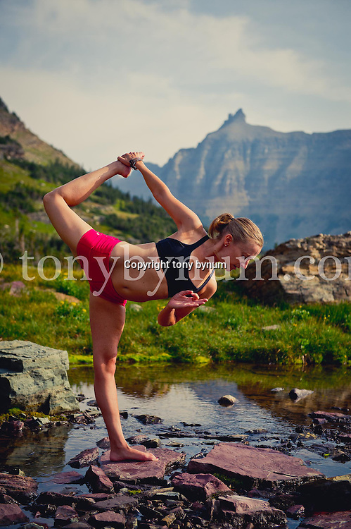 young woman in single leg blance yoga pose in stream, glacier national park