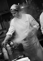 In the chaos of the kitchen, a sous chef is calm, letting her trained hands guide her to making one of the signature dishes that Restaurant Eighteen serves.