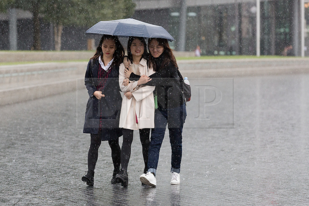 © Licensed to London News Pictures. 01/10/2016. LONDON, UK.  Three women share an umbrella on the south bank in London during heavy rain and wet weather this morning.  Photo credit: Vickie Flores/LNP