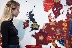 "© Licensed to London News Pictures. 15/01/2019. LONDON, UK. A staff member views ""More in Europe: Europe 2019"", by Yanko Tihov at the Tag Fine Arts stand.  Preview of London Art Fair 2019 at the Business Design Centre in Islington.  The annual fair showcases exceptional modern and contemporary art from the 20th century to present day and opens 16 to 20 January.  Photo credit: Stephen Chung/LNP"