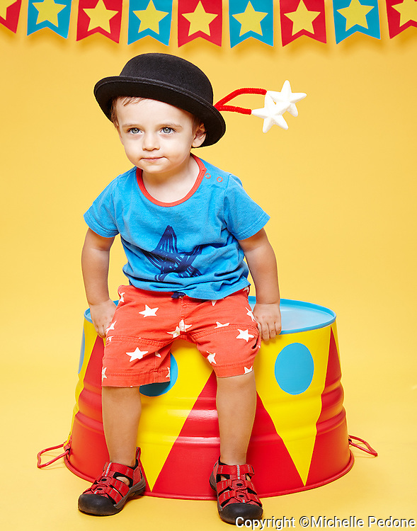 Lorenzo wearing black star hat sitting on a circus pedestal.<br /> Shot at Photoville Photo Booth, September 20, 2015