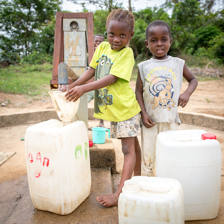 A young girl pumps water and a boy stands next to her,  watching, both pose for the camera in Ganta, Liberia