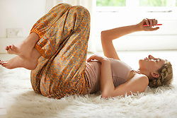 Young Woman Lying on Rug Using Smartphone