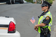 Middletown, New York - A Middletown police officer watches  as marchers in the Middletown-Town of Wallkill Memorial Day parade head down Highland Avenue on May 25, 2015.