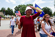 """A demonstrator dressed like a character from the dystopian novel """"The Handmaid's Tale"""" marches in the Families Belong Together rally in downtown Dallas."""