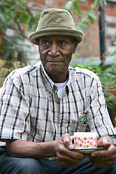 Older man sitting  in the garden having a cup of coffee,