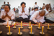 "30 JANUARY 2013 - PHNOM PENH, CAMBODIA:  Cambodian women wearing white mourning clothing pray for late Cambodian King Norodom Sihanouk in Phnom Penh. Sihanouk (31 October 1922 - 15 October 2012) was the King of Cambodia from 1941 to 1955 and again from 1993 to 2004. He was the effective ruler of Cambodia from 1953 to 1970. After his second abdication in 2004, he was given the honorific of ""The King-Father of Cambodia."" Sihanouk held so many positions since 1941 that the Guinness Book of World Records identifies him as the politician who has served the world's greatest variety of political offices. These included two terms as king, two as sovereign prince, one as president, two as prime minister, as well as numerous positions as leader of various governments-in-exile. He served as puppet head of state for the Khmer Rouge government in 1975-1976. Most of these positions were only honorific, including the last position as constitutional king of Cambodia. Sihanouk's actual period of effective rule over Cambodia was from 9 November 1953, when Cambodia gained its independence from France, until 18 March 1970, when General Lon Nol and the National Assembly deposed him. Upon his final abdication, the Cambodian throne council appointed Norodom Sihamoni, one of Sihanouk's sons, as the new king. Sihanouk died in Beijing, China, where he was receiving medical care, on Oct. 15, 2012. His cremation is scheduled to take place on Feb. 4, 2013. Over a million people are expected to attend the service.        PHOTO BY JACK KURTZ"