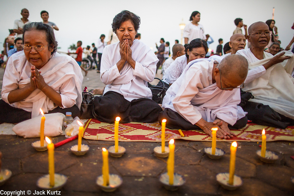 """30 JANUARY 2013 - PHNOM PENH, CAMBODIA:  Cambodian women wearing white mourning clothing pray for late Cambodian King Norodom Sihanouk in Phnom Penh. Sihanouk (31 October 1922- 15 October 2012) was the King of Cambodia from 1941 to 1955 and again from 1993 to 2004. He was the effective ruler of Cambodia from 1953 to 1970. After his second abdication in 2004, he was given the honorific of """"The King-Father of Cambodia."""" Sihanouk held so many positions since 1941 that the Guinness Book of World Records identifies him as the politician who has served the world's greatest variety of political offices. These included two terms as king, two as sovereign prince, one as president, two as prime minister, as well as numerous positions as leader of various governments-in-exile. He served as puppet head of state for the Khmer Rouge government in 1975-1976. Most of these positions were only honorific, including the last position as constitutional king of Cambodia. Sihanouk's actual period of effective rule over Cambodia was from 9 November 1953, when Cambodia gained its independence from France, until 18 March 1970, when General Lon Nol and the National Assembly deposed him. Upon his final abdication, the Cambodian throne council appointed Norodom Sihamoni, one of Sihanouk's sons, as the new king. Sihanouk died in Beijing, China, where he was receiving medical care, on Oct. 15, 2012. His cremation is scheduled to take place on Feb. 4, 2013. Over a million people are expected to attend the service.        PHOTO BY JACK KURTZ"""