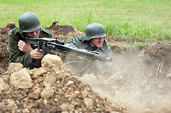 Renactors portray German troops manning an MG42 machine gun from a pre prepared dug in position during a world war two battle reenactment at the Spam Wartime Weekend in Heckmondwyke<br />