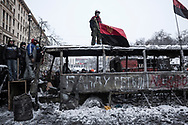 From atop a burnt police bus, Petro Oleïnik (C) watches police line up during stand-off between anti government protesters manning barricades and riot police on Hrushevskoho street, near Maidan Square, in Kiev. 22 January 2014.