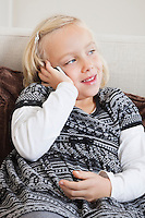 Young girl using cell phone on sofa