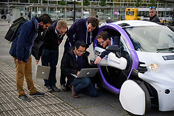© London News Pictures. 11/10/2016. Milton Keynes, UK. A team of technicians examine data during testing of a driverless car around pedestrian areas in Milton Keynes in the first public test of autonomous electric vehicles in the UK. The vehicles have been developed by the Oxford Robotics Institute and Oxbotica. Photo credit: Ben Cawthra/LNP