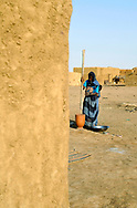 A woman pounding millet in a village in Gorgol province.In order to produce enough food to sustain communities through the long dry seasons in the Western Sahel, agricultural activities depend on the cycles of seasonal rains. Global warming and climate change have caused rainy seasons to fail, erratic rains when they do come and prolonged drought in recent years, exacerbating food insecurity, hunger and poverty in the region.<br />