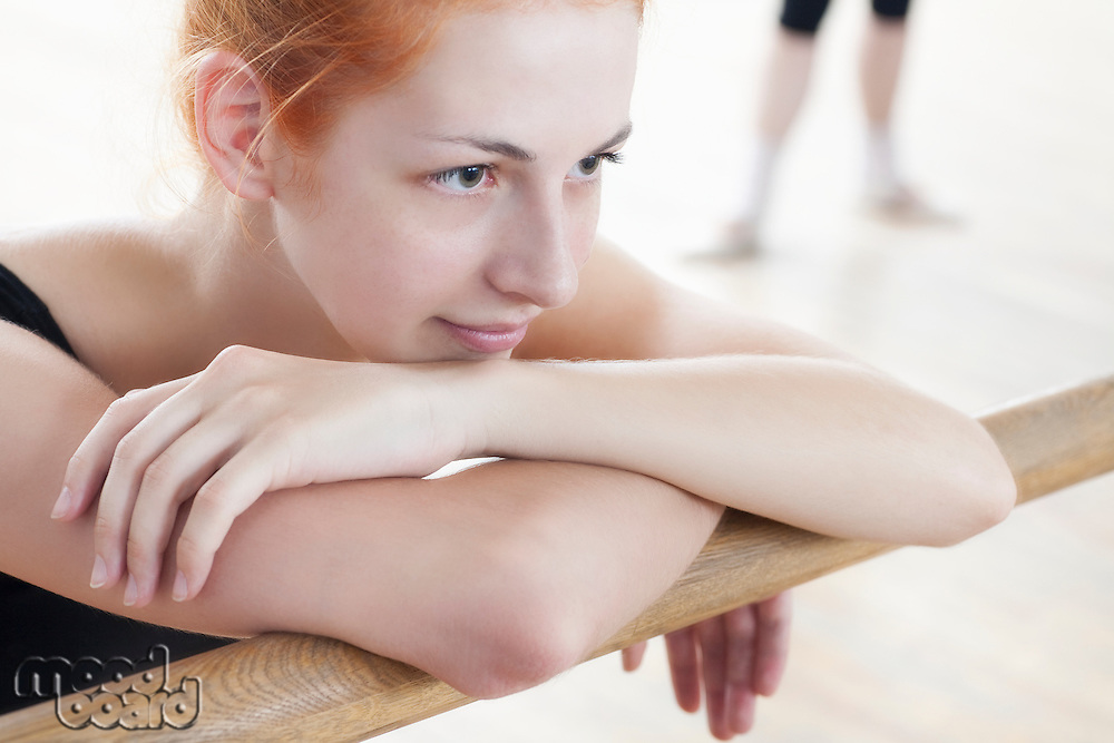 Young woman leans on ballet barre at mirror in rehearsal room