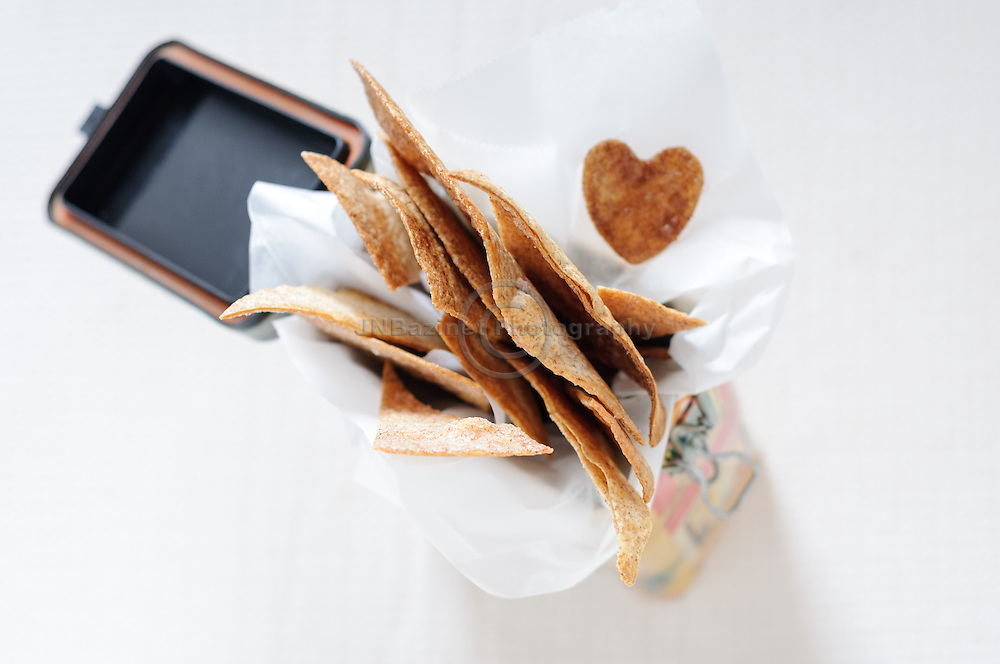 Tin of homemade cinnamon tortilla crisp wedges with one heart-shaped.