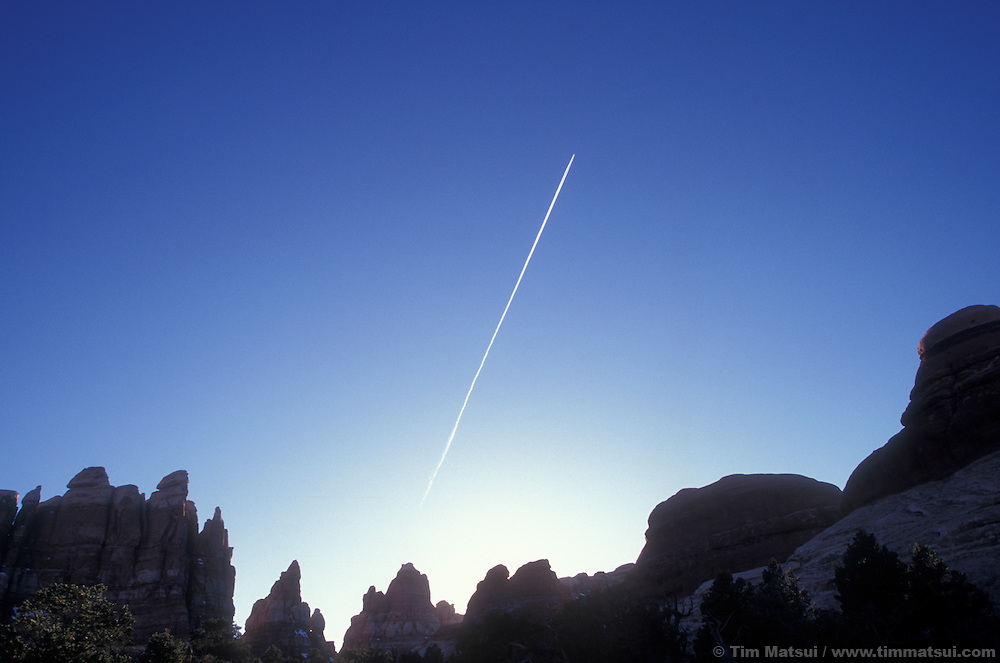 A jet streaks across the sky over the Needles District of Canyonlands National Park.