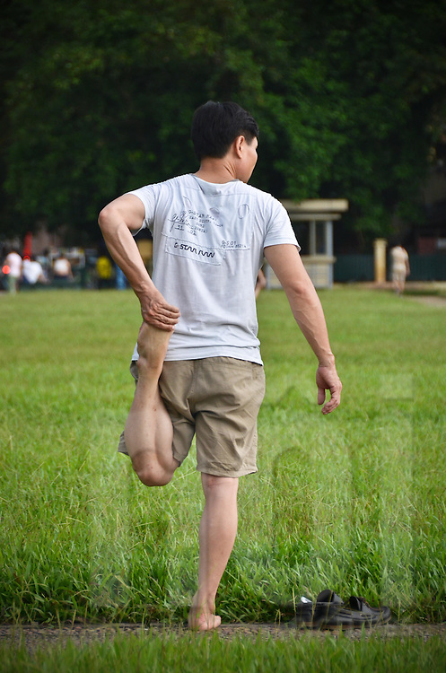 A man is stretching his left leg, standing on his right leg, on the grass  in front of Ho Chi Minh mausoleum in Hanoi.