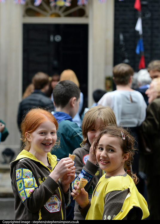 © Licensed to London News Pictures. 03/06/2012. London, UK. Girls eat ice cream on Downing Street. The UK Prime Minister hosts a street party on Downing Street today. The party was moved inside number 10 due to the weather but the PM came onto the street to play games with the children who had gathered.  The Royal Jubilee celebrations. Great Britain is celebrating the 60th  anniversary of the countries Monarch HRH Queen Elizabeth II accession to the throne this weekend Photo credit : Stephen Simpson/LNP