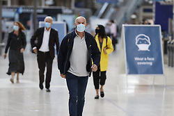 © Licensed to London News Pictures. 15/06/2020. London, UK. Passengers wearing face masks arrive at Waterloo Station. New rules allowing some non-essential retail businneses to open and mandatory face masks on public transport have started today. Photo credit: Peter Macdiarmid/LNP