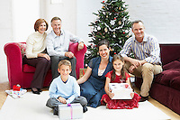 Family sitting by christmas tree in living room portrait