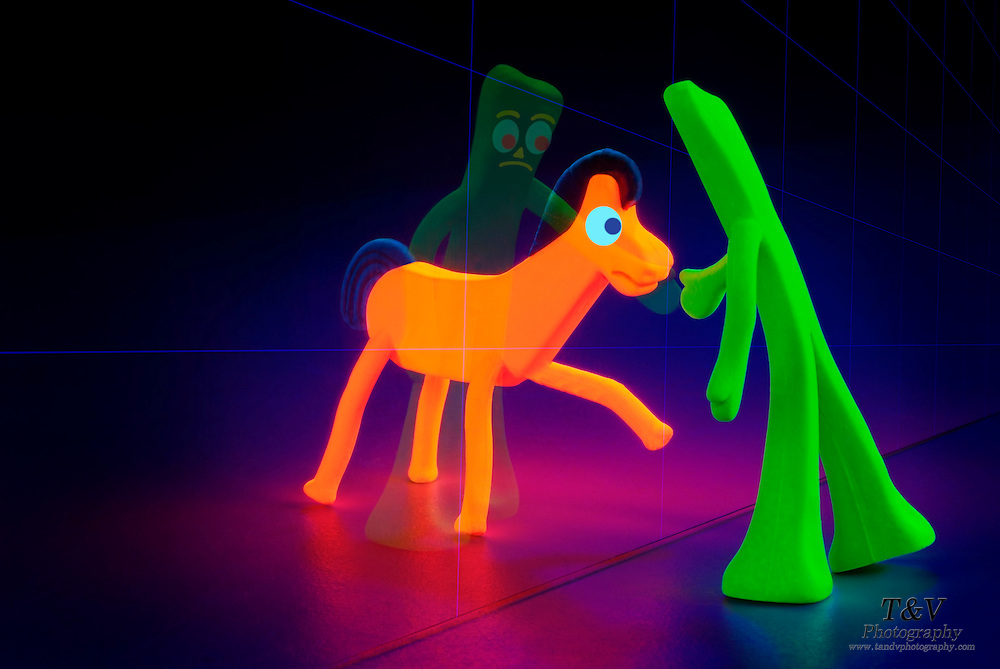 Glowing Gumby and Pokey separated by a wall of glass.Black light