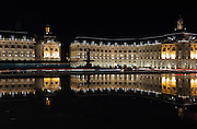 Place de la Bourse (Stock Exchange Square) or Place Royale at night, built 1730-55 by architect Ange-Jacques Gabriel during the reign of King Louis XV, Bordeaux, Aquitaine, France. The royal square is a symmetrical rectangular space with the Stock Exchange to the North, Farms Hall to the East, a central building to the West and the Garonne River to the South. The buildings are reflected in the Miroir d'Eau, a 130x42m reflecting pool by Michel Corajoud and J M Llorca, inaugurated in 2006. The square forms part of the Port of the Moon and is listed as a UNESCO World Heritage Site, and the buildings are listed as historic monuments. Picture by Manuel Cohen