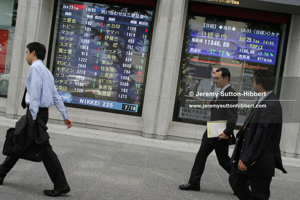Japanese business men, known as salarymen, walk past a bank stocks and shares monitor screen, showing the latest values of commodities, in Marunouchi district, Tokyo, Japan.
