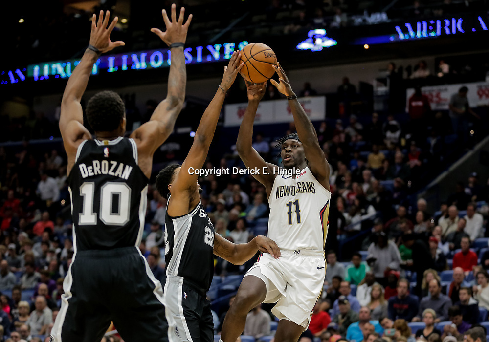 Nov 19, 2018; New Orleans, LA, USA; New Orleans Pelicans guard Jrue Holiday (11) passes as San Antonio Spurs forward Rudy Gay (22) and guard DeMar DeRozan (10) defend during the first quarter at the Smoothie King Center. Mandatory Credit: Derick E. Hingle-USA TODAY Sports
