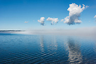 Fog clearing from surface of tranquil lake to reveal blue water under blue sky, Yellowstone Lake, WY, © 2005 David A. Ponton