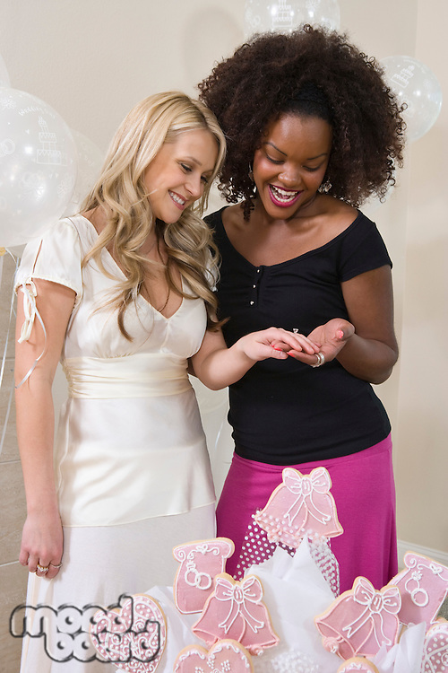 Bride showing friend her engagement ring at Bridal Shower