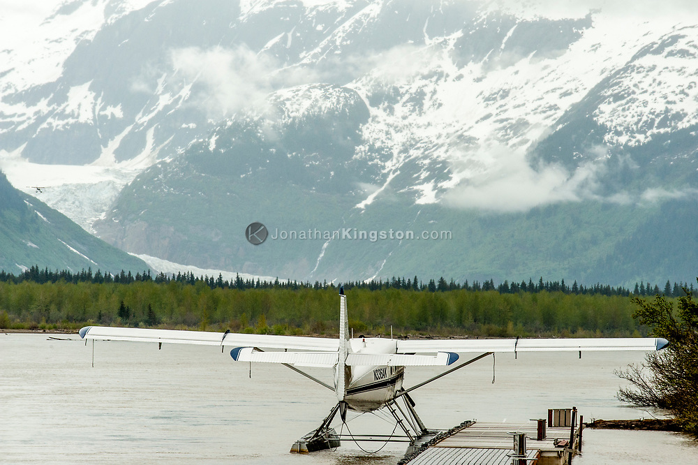 A float plane anchored at a dock with a glacier in the background.