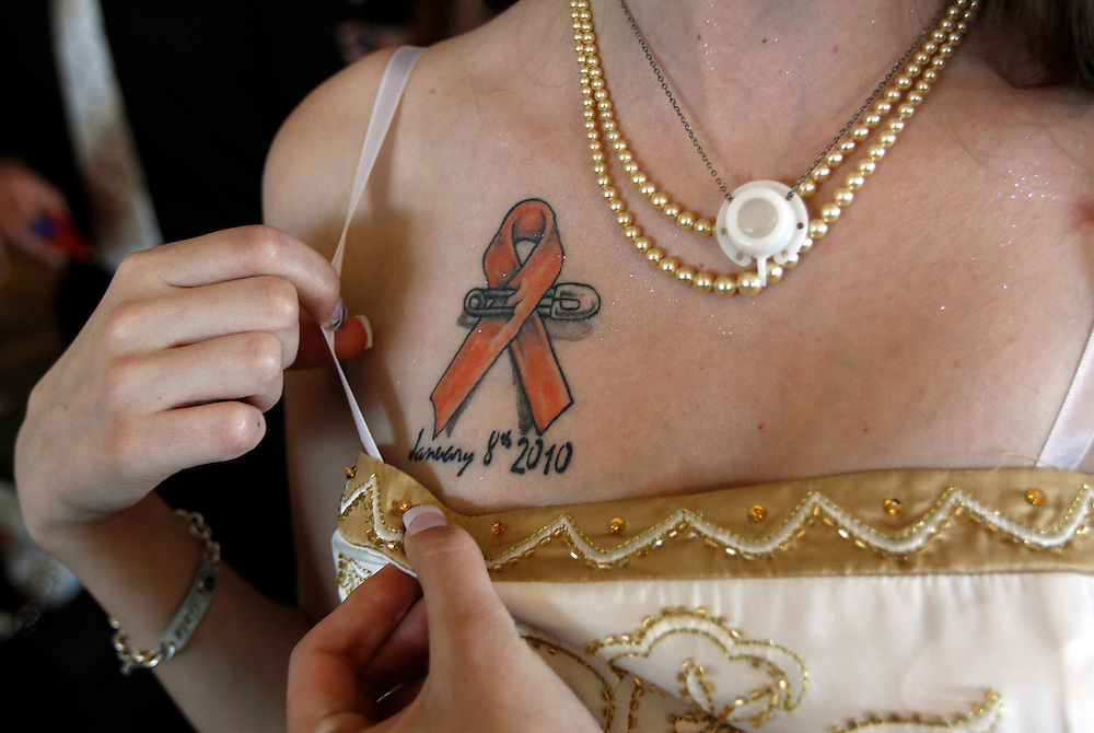 Gaia Damerst shows a leukemia tattoo next to her mediport necklace as she prepared for The Children's Hospital sponsored prom for cancer patients in Denver June 8, 2010.  The mediport was implanted in Damerst, a leukemia cancer survivor, to administer chemotherapy and she made it into a pendant to wear around her neck after it was removed when her treatment ended January 8, 2010 as shown on the tattoo.  REUTERS/Rick Wilking (UNITED STATES)
