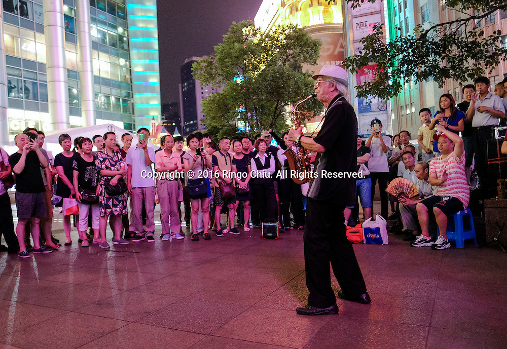 "A performer plays the saxophone in the Nanjing Road Pedestrian Street on September 5, 2016, in Shanghai, China. Nanjing Road is the main shopping street of Shanghai, China, and is one of the world's busiest shopping streets. The street is named after the city of Nanjing, capital of Jiangsu province neighbouring Shanghai. Today's Nanjing Road comprises two sections, Nanjing Road East and Nanjing Road West. In some contexts, ""Nanjing Road"" refers only to what was pre-1945 Nanjing Road, today's Nanjing Road East, which is largely pedestrianised. Before the adoption of the pinyin romanisation in the 1950s, its name was rendered as Nanking Road in English. Shanghai is the most populous city in China and the most populous city proper in the world. It is one of the four direct-controlled municipalities of China, with a population of more than 24 million as of 2014. It is a global financial centre, and a transport hub with the world's busiest container port. Located in the Yangtze River Delta in East China, Shanghai sits on the south edge of the mouth of the Yangtze in the middle portion of the Chinese coast. The municipality borders the provinces of Jiangsu and Zhejiang to the north, south and west, and is bounded to the east by the East China Sea. A major administrative, shipping, and trading town, Shanghai grew in importance in the 19th century due to trade and recognition of its favourable port location and economic potential. The city was one of five forced open to foreign trade following the British victory over China in the First Opium War while the subsequent 1842 Treaty of Nanking and 1844 Treaty of Whampoa allowed the establishment of the Shanghai International Settlement and the French Concession. The city then flourished as a center of commerce between China and other parts of the world (predominantly Western countries), and became the primary financial hub of the Asia-Pacific region in the 1930s. However, with the Communist Party takeover of the mainland in 194"