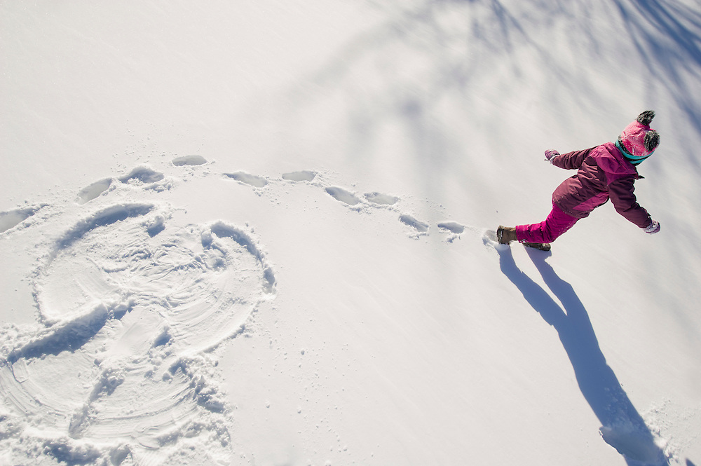 A child making a snow angel in an open field of untracked snow.